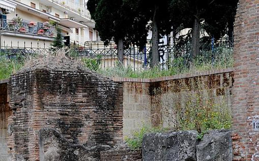 Modern-day apartment buildings line the roads just outside the fence surrounding the Flavio amphitheater, found in the center of Pozzuoli, Italy. The theater is thought to have been constructed during the era of emperor Vespasian, from 70 to 79.