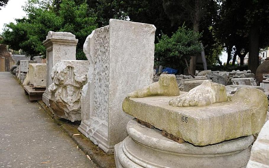 A row of inventoried columns, statues and headstones seem to haphazardly lie in at the entrance of the Flavio amphitheater - they have been cataloged but not organized for display.