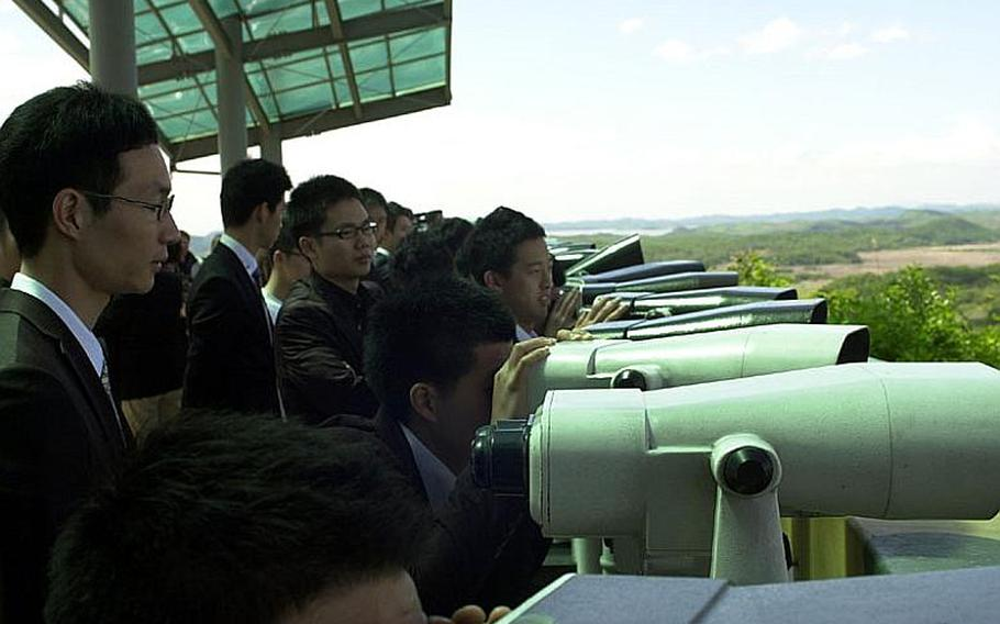 Visitors to the Dora Observatory at Korea's Demilitarized Zone use binoculars to look into North Korea on Wednesday. Tours to the DMZ continue apparently unaffected by rising tensions between North Korea and South Korea.