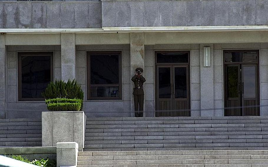 A North Korean soldier uses binoculars to keep an eye on a visiting group of teenagers on the South Korea side of the Demilitarized Zone on Wednesday. Tourists are still allowed at the Joint Security Area of the DMZ despite rising tensions between the two Koreas.