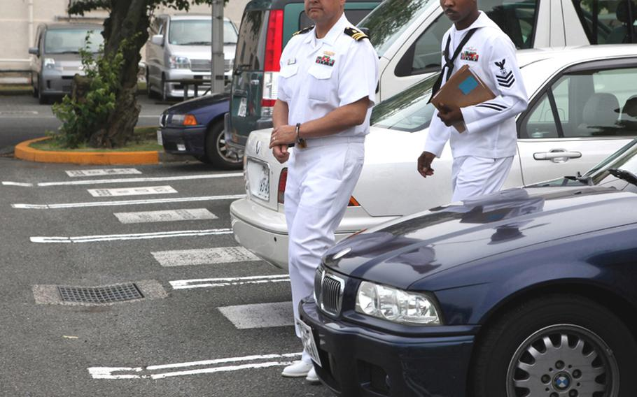 Navy Lt. Cmdr. Anthony Velasquez is escorted from the Yokosuka Naval Base court Wednesday after being found guilty on two counts of wrongful sexual contact and two counts of conduct unbecoming an officer.