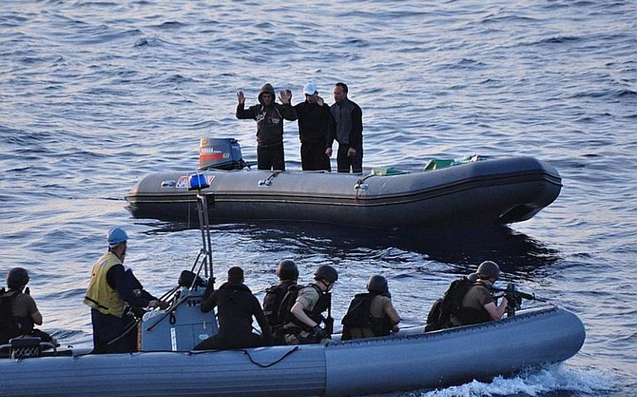 Suspected smugglers surrender to a search-and-seizure team from USS Elrod. A helicopter from the ship spotted the suspects dumping what turned out to be hundreds of pounds of narcotics overboard in the waters off the coast of Morocco Tuesday night. The suspects and drugs were turned over to Moroccan officials.