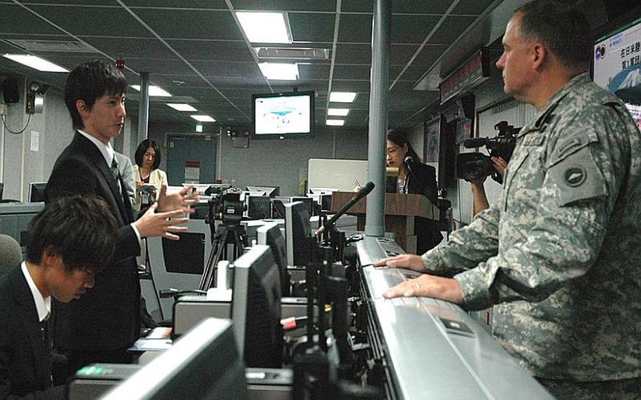 A Heisei International University student talks Friday with Maj. Gen. Francis Wiercinski, the U.S. Army?s commander in Japan, inside the Army's command and control room at Camp Zama. The students toured the base Friday as part of their thesis seminar about the U.S.-Japan alliance.