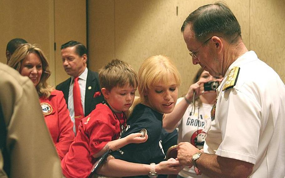 """Adm. Mike Mullen, chairman of the Joint Chiefs of Staff, hands a coin to one of the roughly 375 children who lost a loved one in the military who attended """"Good Grief Camp"""" Friday run by the Tragedy Assistance Program for Survivors."""