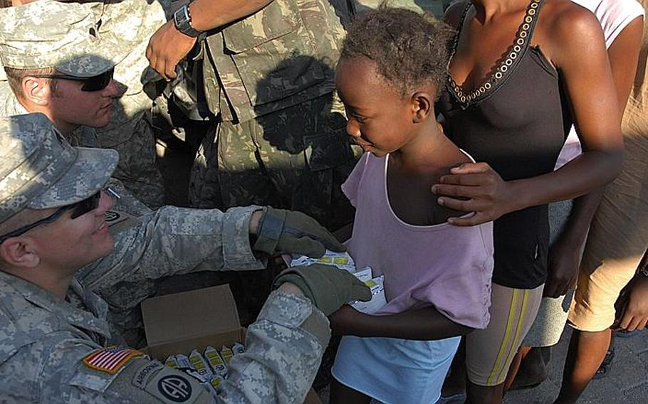 Sgt. Otis Richardson, Company A, 1st Battalion, 325th Airborne Infantry Regiment, hands out World Food Program high-calorie biscuits to children in City Soleil, one of Haiti's toughest neighborhoods. The Army is working in the area with a Brazilian contingent of UN soldiers.