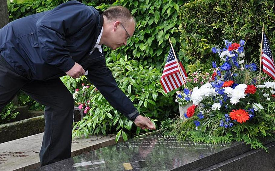 Mark Lievense of the Bamberg, Germany, VFW on Sunday places flowers on the grave of Nathan R. Preston,  the city's first US military governor and resident officer following World War II.