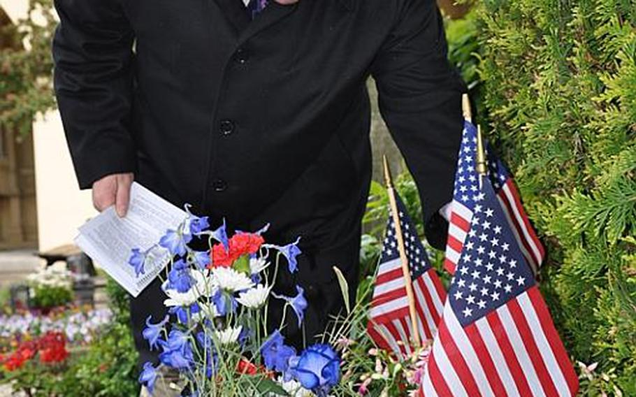 Dave Robinson, commander of VFW Post 10592 VFW in Bamberg, Germany, places a  flag on the grave of Nathan R. Preston, the city's first U.S. military governor and resident officer following World War II.