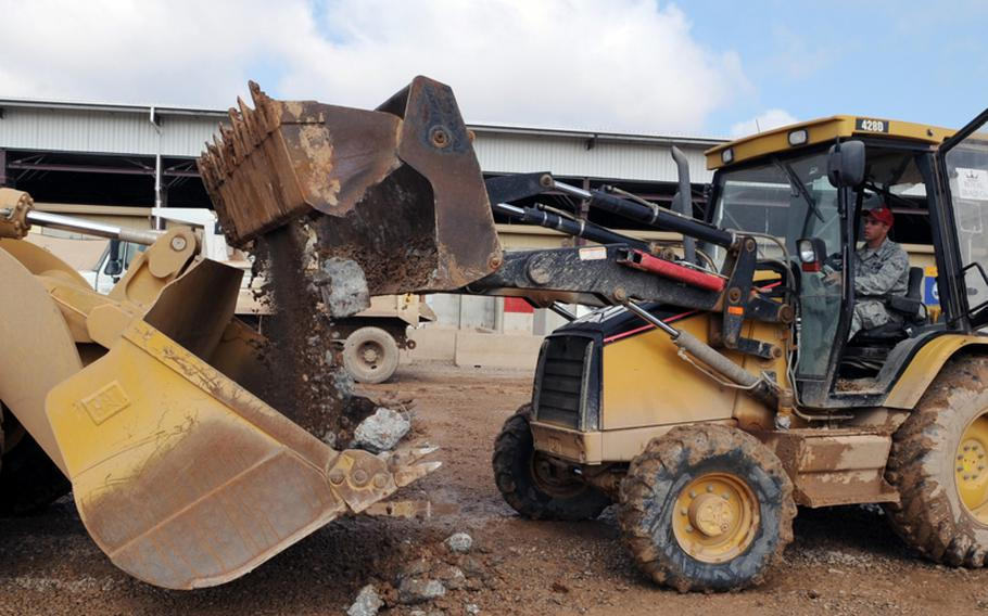 Airman Britton Busbee removes dirt and rocks from a parking lot during construction of the transient village at Joint Base Balad, Iraq, on March 2.