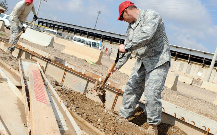 Capt. Ben Knost, right, and Master Sgt. Greg Platt shovel dirt during construction of a transient village at Joint Base Balad, Iraq, on March 2, 2010.