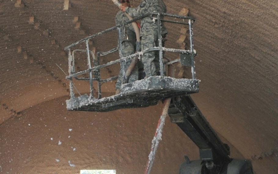 Staff Sgt. Juan Robles, left, and Master Sgt. Chip Koons spray acoustic insulation on the ceiling of a building during construction of a transient village at Joint Base Balad, Iraq, on March 31.