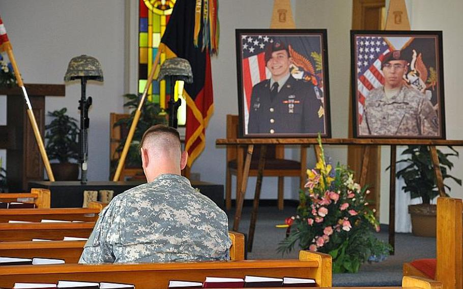 A soldier mourns at the Warner Barracks chapel in Bamberg before the memorial ceremony to honor the two most recent combat deaths in the 173rd Airborne Brigade Combat Team, Spc. Matthew Hennigan (left) and Spc Louis Fastuca. Both were promoted to sergeant, and unit officials altered the soldiers' photos to add their new ranks.