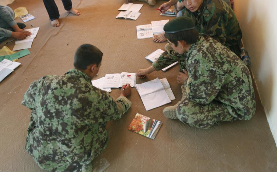 Two Afghan National Army soldiers go over their work during the two-hour literacy class at the Garmsir District governor's compound in Hazer Joft, Garmsir District, Helmand province, Afghanistan, July 4, 2010. The program benefits the ANA and ANP both by learning how to read and write and also they get $30 extra a month.