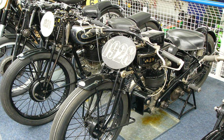 A 1928 AJS motorcycle, right, drips oil waiting for the next time it will be taken for a spin at the Hockenheimring.