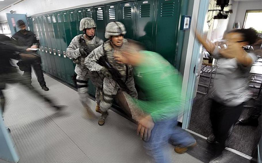Master Sgt. Thomas Rood, center front, and Staff Sgt. Shane Brown rush role players acting as hostages out of a classroom during a drill in Edgren High School at Misawa Air Base, Japan, on Thursday.