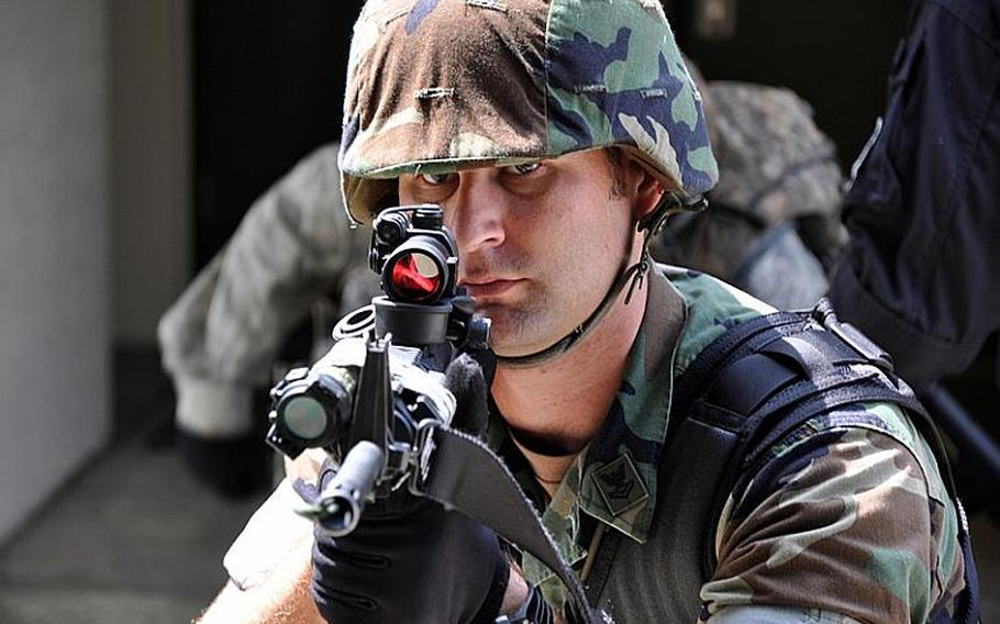 Petty Officer 2nd Class Daniel Frericks, a master-at-arms, covers the area of threat during a training drill at Misawa Air Base, Japan, on Thursday.