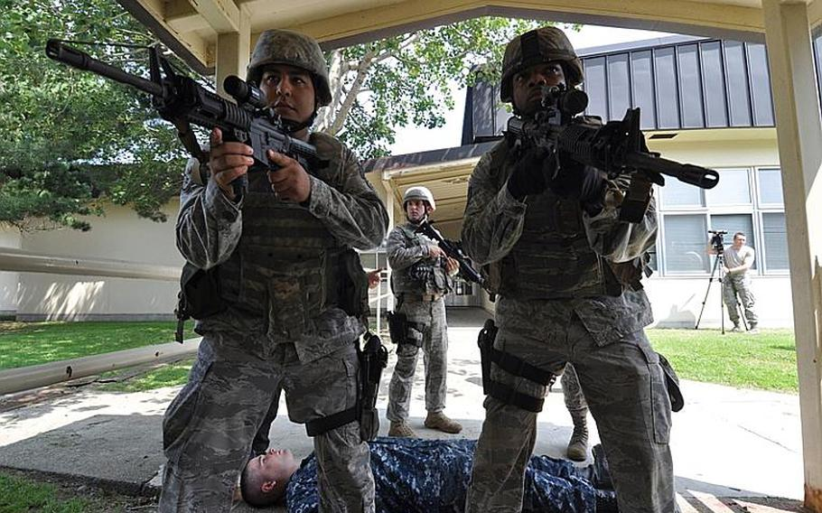 Staff Sgt. Anthony Santillan, left, and Tech Sgt. Chris Jones places themselves between a wounded victim and the direction of the threat during a training course at Misawa Air Base, Japan, on Thursday.