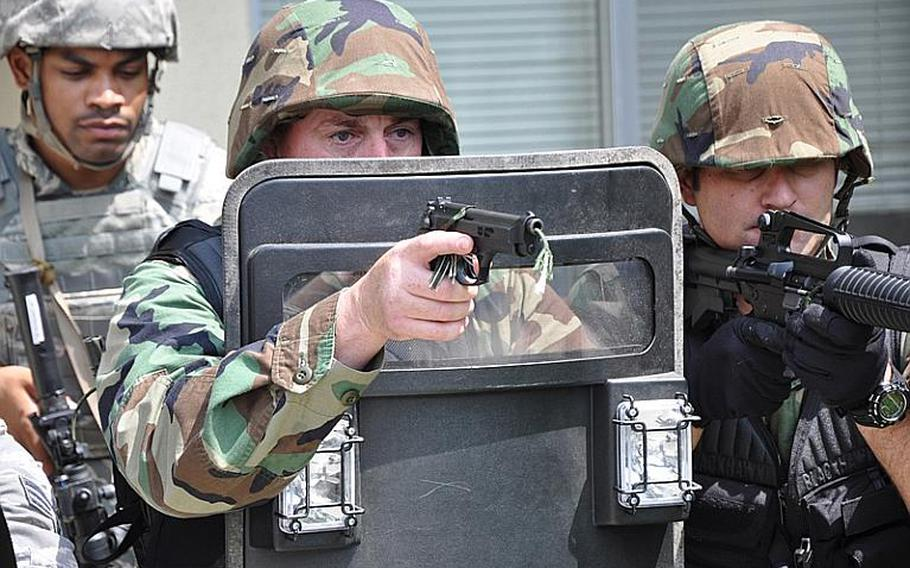 Navy Petty Officer 1st Class Jason Clark, a master-at-arms, holds a ballistic tactical shield during a drill at Misawa Air Base, Japan, on Thursday.