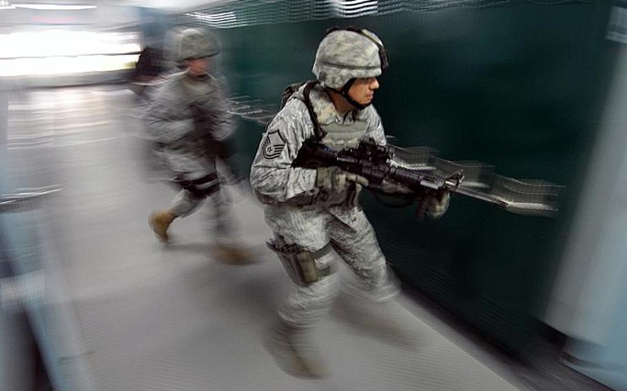 Master Sgt. Thomas Rood, right, races down the hallway at Edgren High School on Misawa Air Base, Japan, on Thursday during an active-shooter training drill.