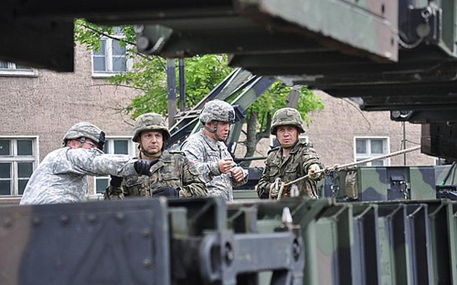 Soldiers from U.S. Army Europe's 5th Battalion, 7th Air Defense Artillery Regiment out of Kaiserslautern, Germany, familiarized members of the Polish military last month on how to load and unload Patriot missile canisters in Morag, Poland. From left to right: U.S. Army Spc. Steven R. Faddis, Polish air force Capt. Basuk Krzyszt, U.S. Army Spc. Anthony R. Doty, and Polish land force Capt. Bogdan Wludarczyk.