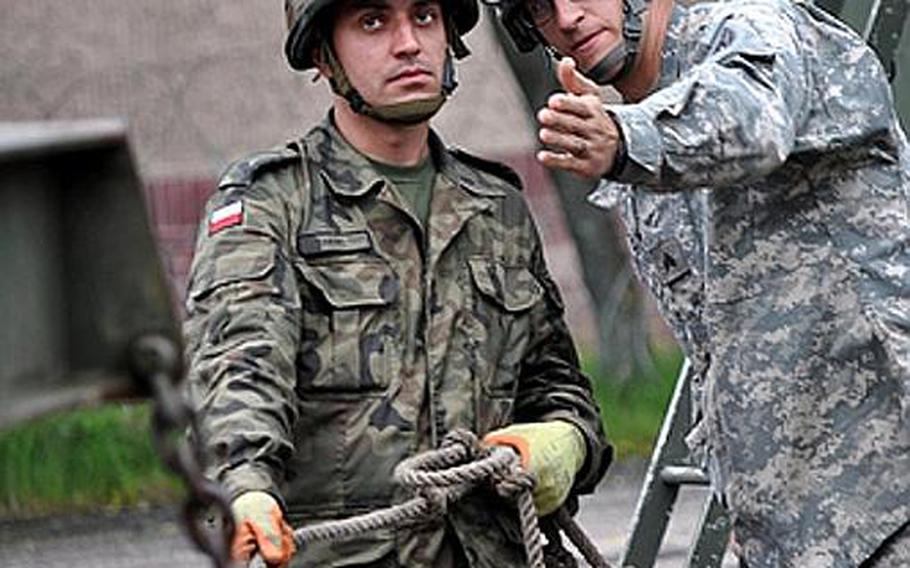 Polish air force Warrant Officer 3rd Class Tomasz Herc, left, and U.S. Army Sgt. Dustin P. Sigmon from Sherrills Ford, N.C., negotiate a Patriot missile canister during recent training in Morag, Poland. Soldiers from U.S. Army Europe's 5th Battalion, 7th Air Defense Artillery Regiment out of Kaiserslautern, Germany, are familiarizing the Polish military on the Patriot missile system. The training is designed to improve Polish air defense capabilities while also developing the skills of U.S. Patriot crew members.