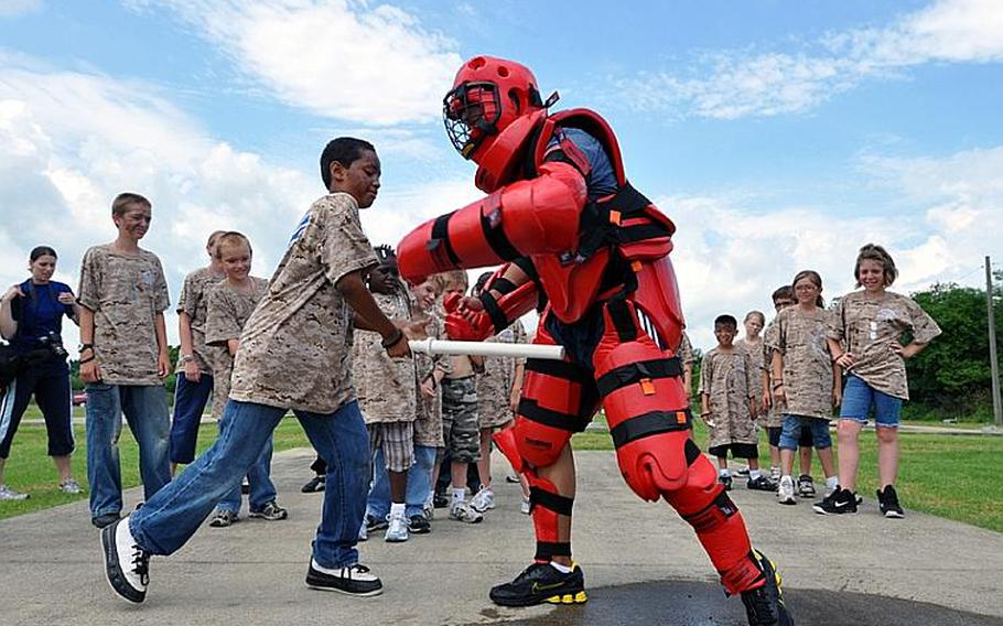 Jayden Gardner, 10, strikes a security forces volunteer with a baton in a training session during Operation CODE on Saturday at Misawa Air Base, Japan.