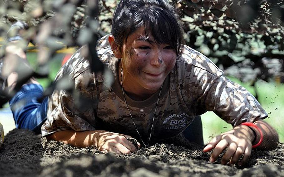 Chyanna Colburn, 12, crawls under cargo netting while running through an obstacle course in Saturday's Operation CODE at Misawa Air Base, Japan.