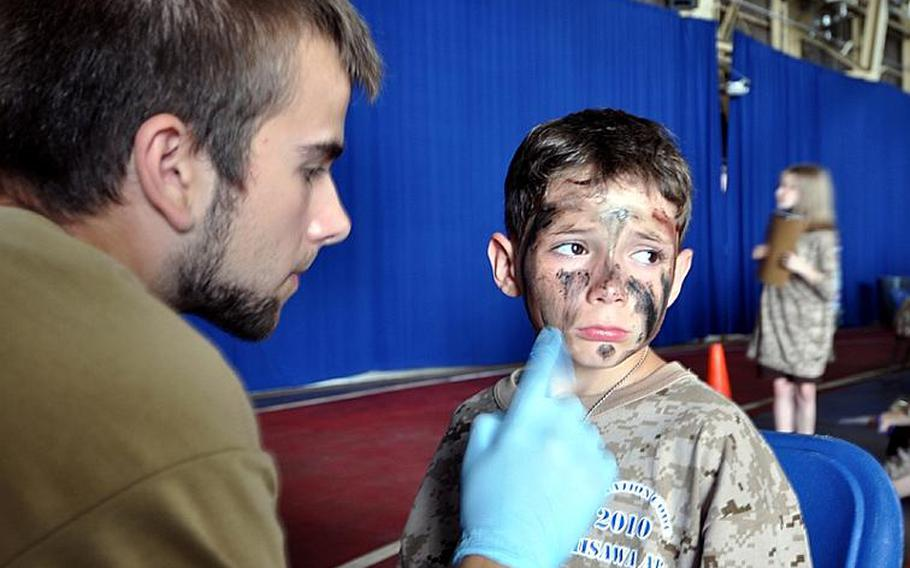 Alex Schneider sits patiently while Jordan Rude puts camouflage paint on his face Saturday during Operation CODE, a simulated deployment exercise for youth at Misawa Air Base, Japan.