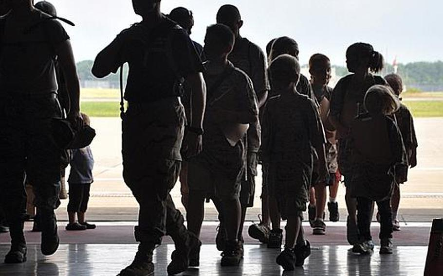 Children and volunteers are silhouetted as they walk into Hangar 949 on Saturday during Operation CODE, a simulated-deployment exercise for base youth at Misawa Air Base, Japan.
