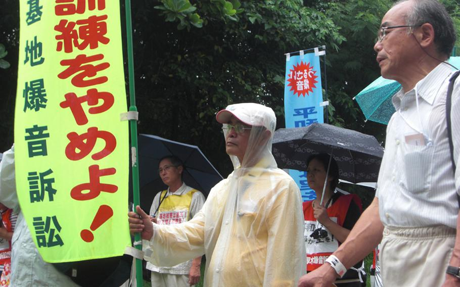 Eisho Nakandakari, center, from Ginowan, Okinawa, stands among about 200 residents and supporters Thursday outside the Fukuoka High Court branch in Naha. The banner he holds demands a stop to flight operations at Marine Corps Air Station Futenma in Ginowan.