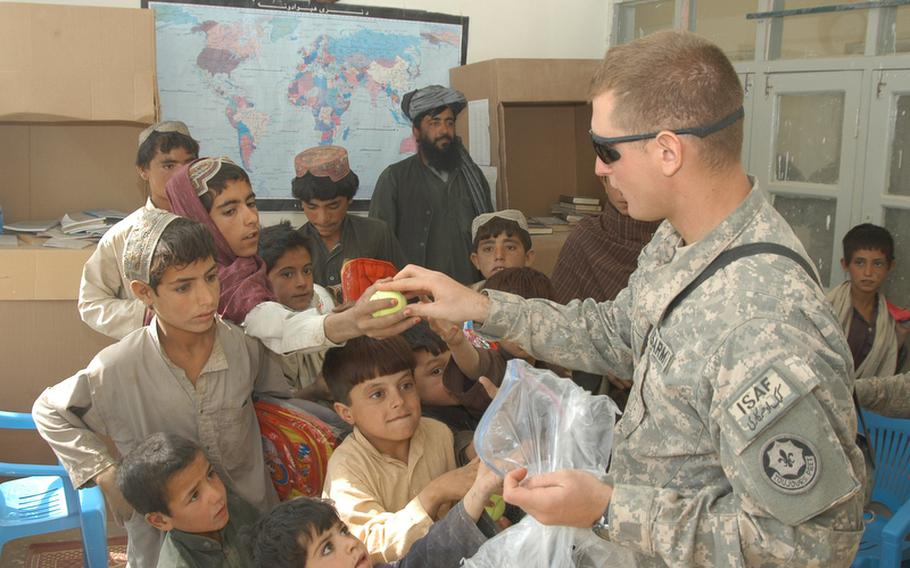 Second Lt. Loris Lepri, the 2nd Platoon leader for K Troop, 4th Squadron, 2nd Stryker Cavalry Regiment, hands out tennis balls at a school in Robat, Afghanistan, during a recent visit. Visiting soldiers also gave two soccer balls to headmaster Fazal Rehman, who is pictured standing in the back.