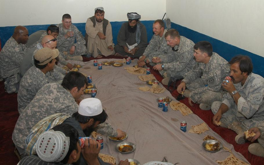 U.S. soldiers, Afghan Highway Police and residents of Robat, a village in southern Afghanistan, share a sheep meal. The flat bread served with the meal was prepared by female U.S. soldiers who were shown how to make it by some of the Afghan women of the village.