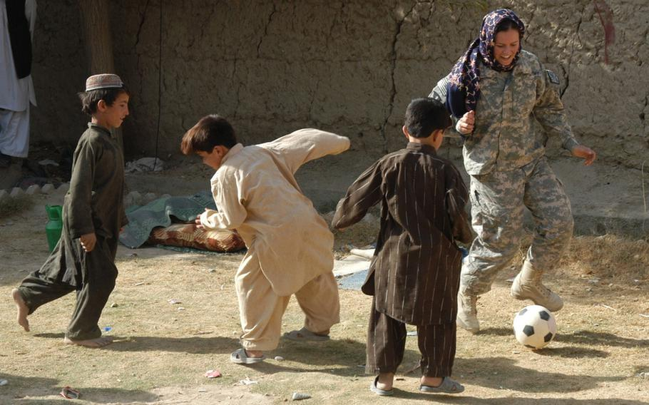 Second Lt. Randy Wintermantel plays soccer with some of the children of Robat, a village in southern Afghanistan, during a recent visit by U.S. soldiers. The soldiers handed out book bags in the nearby school, and female soldiers were shown how to make flat bread by some of the Afghan women of Robat.