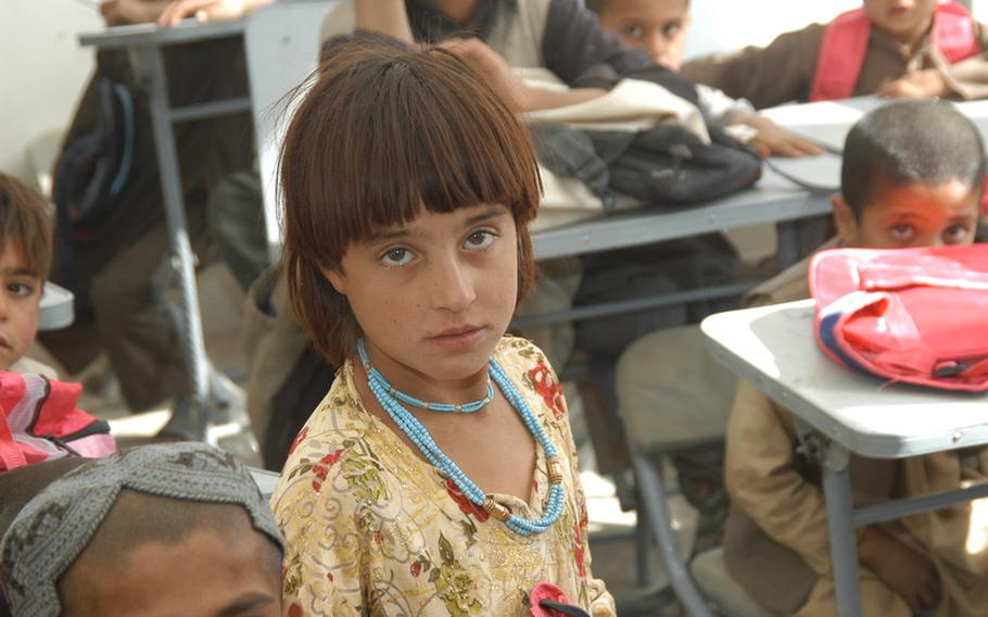 A girl stands in the middle of a classroom in Robat, Afghanistan, where she studies alongside boys, thanks to the relative security of the area. The Taliban believe the education of females is against the teachings of Islam and has bombed and burned hundreds of schools in recent years for teaching girls.