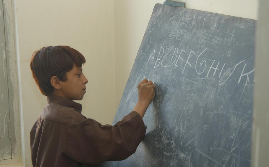A student in Robat, in southern Afghanistan, shows visiting U.S. soldiers how he can write out the English alphabet. Sahib Jan, the most powerful man in the remote village, said in order for a Afghan community to provide education for its children, there must first be security.