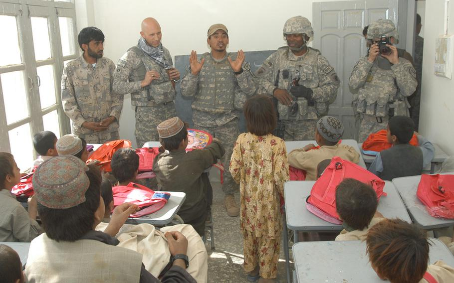 U.S. soldiers and a member of the Afghan Highway Police take questions from students at a school in Robat in southern Afghanistan during a recent visit, during which book bags were handed out to all the children.