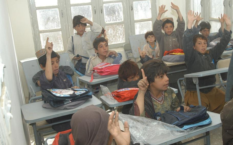Students at a school in Robat, Afghanistan, raise their hands during a session with visiting U.S. soldiers. There are about 15 girls in the school, at least two of which can be seen in this class.