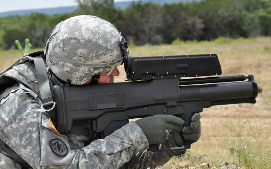 """A soldier demonstrates the  XM25 Counter Defilade Targeting Engagement System at Aberdeen Test Center, Md. The Army has begun testing and training with five of the prototype """"smart"""" weapons in Afghanistan. The weapon fires rounds that can be programmed to explode on impact, in front of or behind an object. Limited production of the XM25 is expected to begin in 2012."""
