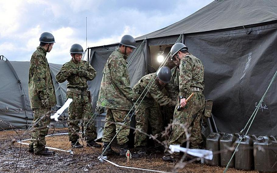 Members of the Japan Ground Self-Defense Force work on a tent at a bivouac site on Misawa Air Base, Japan, on Friday, the first day of Keen Sword 2011. The exercise includes more than 44,000 U.S. and Japanese troops across the country. Misawa's portion of the exercise will focus on a 'guard and protect' mission of the base.