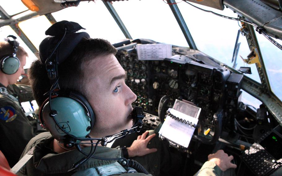 Capt. William Dunn, right, observes the conditions outside his C-130 as it flies toward the Sea of Japan on Monday as part of Keen Sword, a U.S.-Japan training exercise.