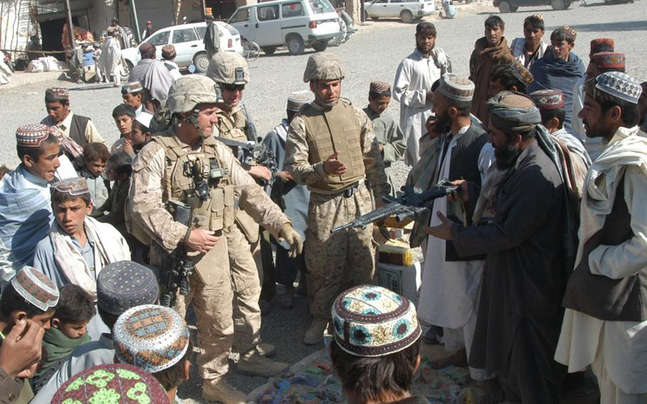 U.S. Marine 1st Lts. Shannon Ashley, left, and Sam Jacobson, next to him, urge a merchant to stop selling realistic-looking toy guns at the Safar Bazaar in the Garmsir District of Helmand Province in Afghanistan. They said the Marines might mistake the toys for a real weapon which could lead to the tragic killing of a local child. The toy weapons were still on sale as the Marines walked away.