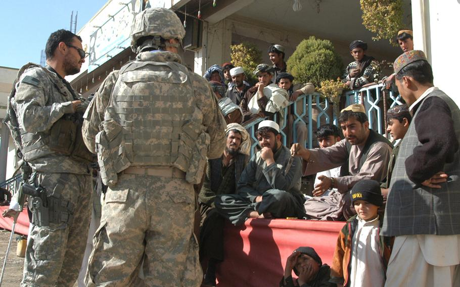 A U.S. servicemember talks with merchants at a travel center along Highway 1 in the Arghandab District of southern Afghanistan, with the help of interpreter to his right. Coalition forces patrol the travel center regularly as part of an effort to keep the Taliban out of the area and to win over the merchants and visitors to the facility.