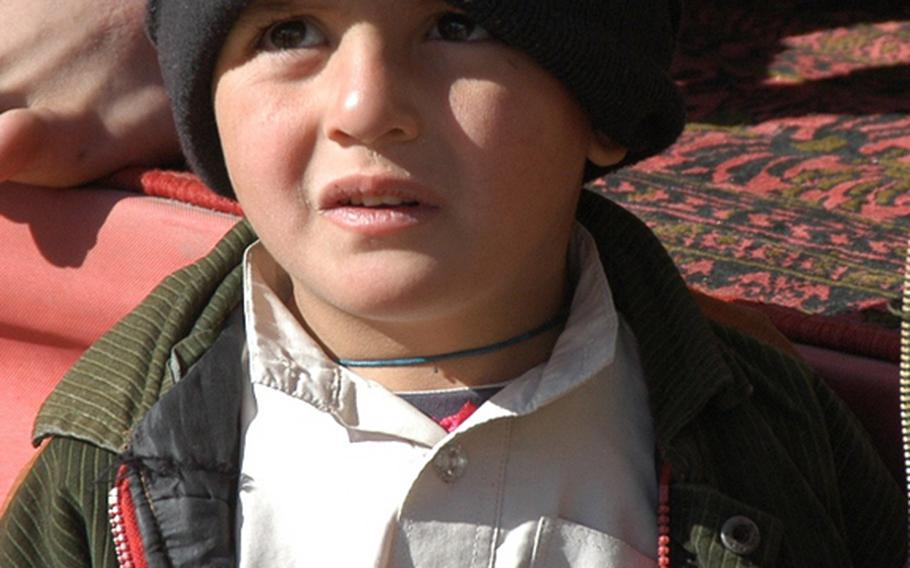 A young boy sports what is presumably a hat bearing the name of U.S. President Obama at a travel center in the Arghandab district of southern Afghanistan.