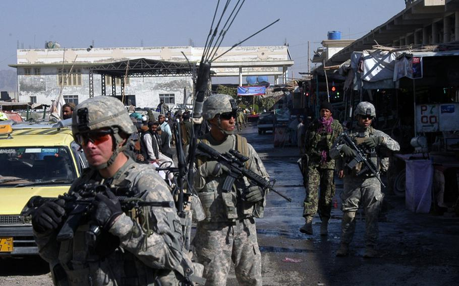 Soldiers from the U.S. and Afghan armies recently patrol a travel center in the Arghandab District of southern Afghanistan, as others take positions on the roof to the upper right. The patrols are done on a regular basis as part of the coalition forces' effort to win over the hearts and minds of the Afghan people.