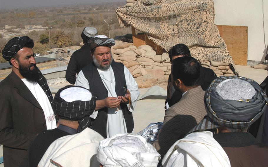 Arghandab District Governor Haji Shah Mohammad, center, talks with residents of his southern Afghanistan region recently on the roof of the district center, which is located inside the gates of a U.S. Army combat outpost. Mohammad said he knows the Taliban wants him dead for the work he does in cooperation with the U.S., but said his efforts are worth the risk because they are for the betterment of his country.