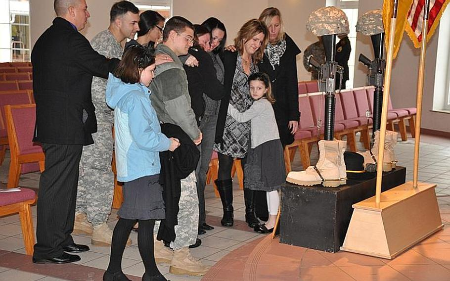 Family and friends of 2nd Stryker Cavalry Regiment soldiers Spc. Kelly J. Mixon and Sgt. James A. Ayube II pay their respects following a memorial service in Vilseck, Germany, on Thursday. Mixon and Ayube were killed Dec. 8 in Balkh province, Afghanistan, from wounds sustained when an insurgent attacked their unit with a bomb, according to a DOD news release.