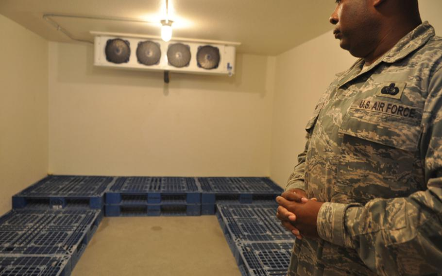 Master Sgt. Hugh Watson Jr. stands in a refrigeration unit at Qatar's Al Udeid Air Base used to store the bodies of troops killed in Iraq and Afghanistan. Nearly every war casualty stops at Al Udeid to receive fresh ice for the onward journey to the United States.