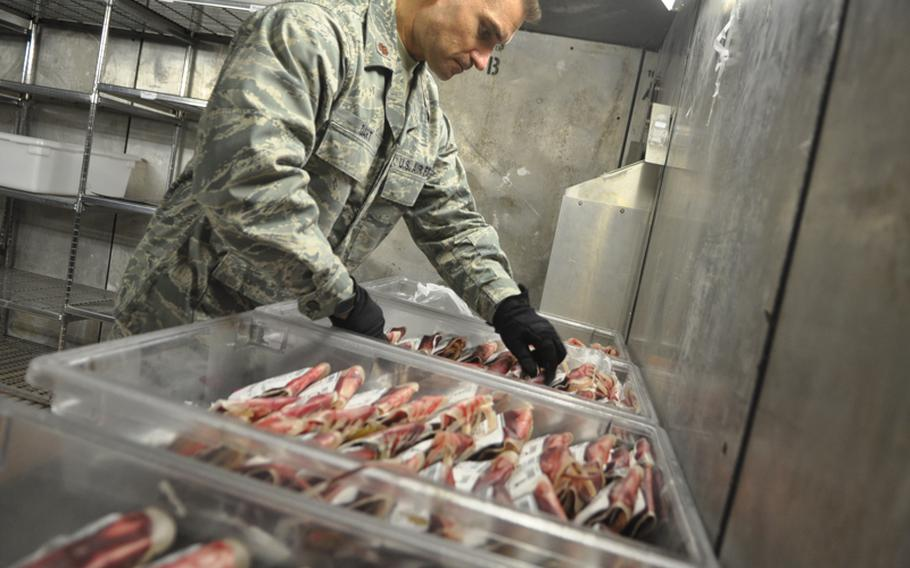 Air Force Maj. Brian Dart, 43, works in the cold storage room of Al Udeid Air Base's blood center to ready a shipment of blood and plasma. Dart oversees the center, which is responsible for processing nearly all of the blood headed to hospitals in Iraq and Afghanistan.