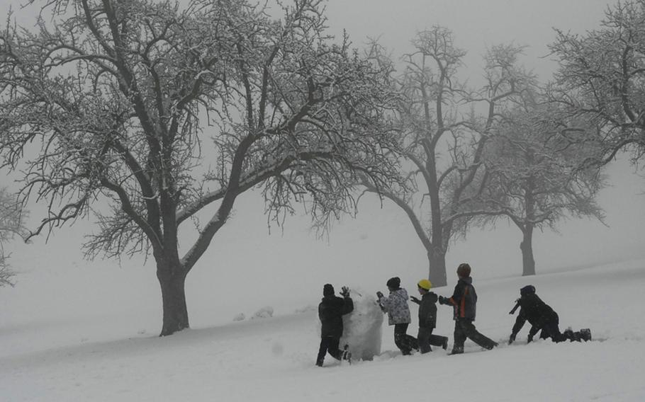 Children roll a snowball down a hill on Robinson Barracks in Stuttgart, Germany, on Monday as they collect snow for a fort they are building. Other children used the hill for sledding and snowball fights during their holiday break.