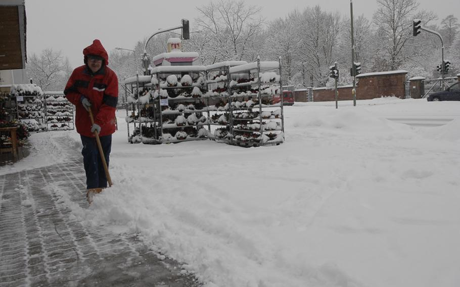 Jorgen Petzler shovels snow outside a flower shop in downtown Kaiserslautern Monday afternoon. The area was hit with another winter storm that snarled traffic throughout out much of the city.