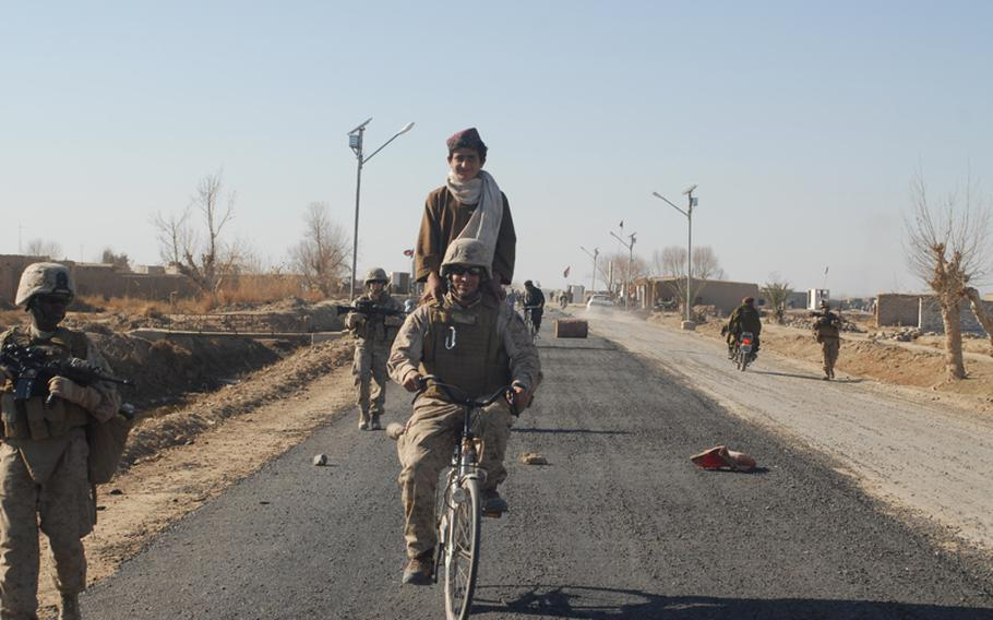 An Afghan translator working for the Marines takes a local boy for a bike ride on the boy's bike on Marjah's main drag. The road had just been paved, a first in the town.